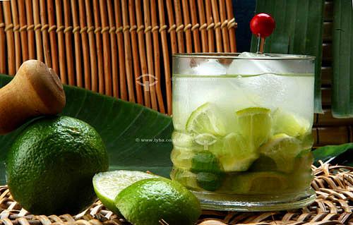 Copo de caipirinha (bebida típica brasileira feita de cachaça, limão e açúcar) e limão cortado ao lado.