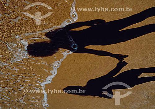 Sombra de um casal de mãos dadas na areia da praia
