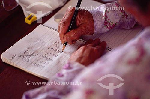 Detalhe de mão de mulher com lápis escrevendo em caderno - alfabetização de adultos - Brasil / Data: 1996