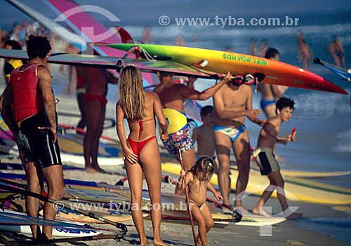 Pessoas na praia e surfistas (windsurf) com suas pranchas