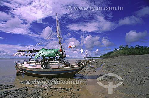 Pescador com a família a bordo, consertando a hélice de seu barco, ancorado durante a maré baixa - planície de lama característica da costa do AP - Janeiro de 2000.  - Amapá - Brasil