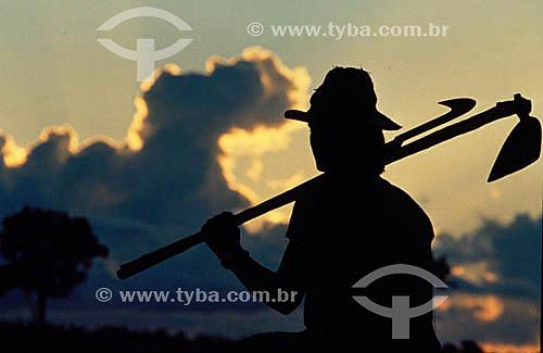 Silhueta de trabalhador rural segurando a foice e a enxada - Amazônia -  Brasil