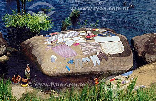 Assunto:  Mulheres secando a roupa lavada sobre uma pedra à beira-rio / Local: São Gabriel da Cachoeira - Rio Negro / Data: 2004