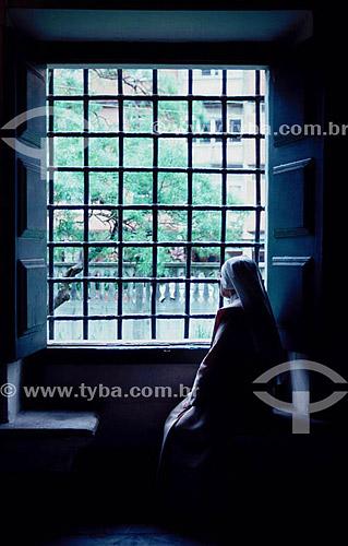 Freira sentada olhando através de janela com grades - Salvador - BA - Brasil  - Salvador - Bahia - Brasil
