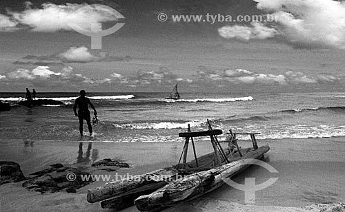 Pescador segurando peixes com jangadas na praia de Itapoa - Salvador - Bahia - Brasil  - Salvador - Bahia - Brasil