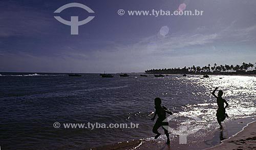Silhueta de dois meninos correndo na praia de Itapoa iluminada pelo  pelo reflexo prateado dopôr-do-sol na água, com barcos e coqueiros ao fundo - Salvador - Bahia - Brasil  - Salvador - Bahia - Brasil