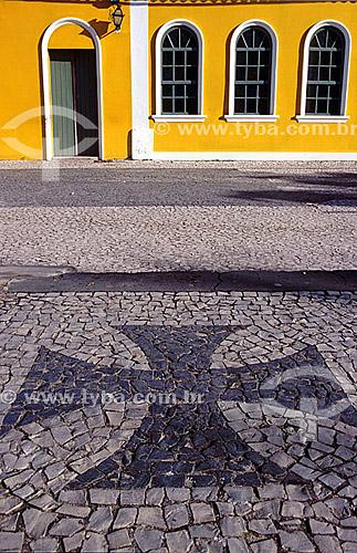 Detalhe de Arquitetura - Calçada em pedra portuguesa com Cruz de Malta, um dos símbolos de Portugal, em mosaico em frente a uma casa amarela de janelas e porta brancas e verdes - Colonização portuguesa - Porto Seguro  - BA - Brasil  A área denominada Costa do Descobrimento (Reserva da Mata Atlântica) é Patrimônio Mundial pela UNESCO desde 01-12-1999 e nela estão localizadas 23 áreas de proteção ambiental Bahia (incluindo Porto Seguro).  - Porto Seguro - Bahia - Brasil