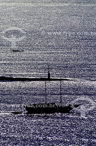 Silhueta de saveiro cruzando o mar prateado pelo pôr-do-sol na Bahia - Brasil  - Porto Seguro - Bahia - Brasil