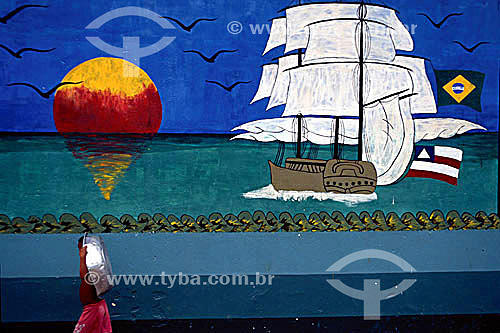 Menino passando com bacia de alumínio na cabeça na frente de painel alusivo ao Descobrimento do Brasil, mostrando uma caravela - Porto Seguro  - litoral sul da Bahia - Brasil  A área denominada Costa do Descobrimento (Reserva da Mata Atlântica) é Patrimônio Mundial pela UNESCO desde 01-12-1999 e nela estão localizadas 23 áreas de proteção ambiental na Bahia (incluindo Porto Seguro).  - Porto Seguro - Bahia - Brasil