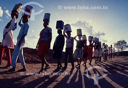 Mulheres com lata na cabeça indo buscar água durante a seca no Nordeste - Ceará - Brasil - Data: 1997
