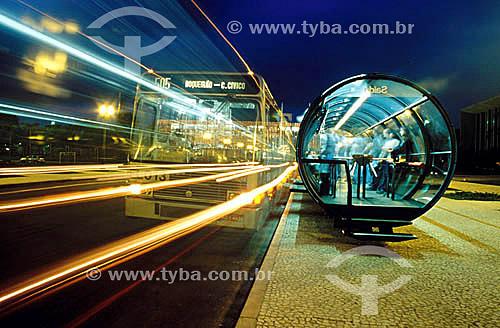 Ônibus passando em velocidade - Pessoas esperando ônibus na estação Tubo para ônibus urbanos em Curitiba - Paraná - Novembro 2000  - Curitiba - Paraná - Brasil