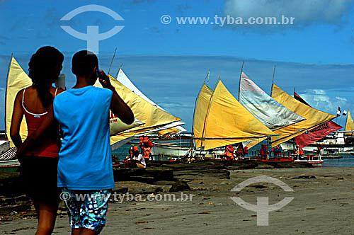 Rapaz falando ao celular enquanto caminha com namorada na praia - jangadas ao fundo - Recife - PE - Brasil  foto digital  - Recife - Pernambuco - Brasil