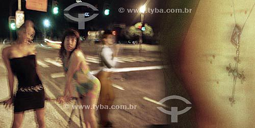 Braço de homem tatuado em primeiro plano e mulheres e travestis seduzindo pedestres à noite no bairro boêmio da Lapa - Rio de Janeiro - RJ - Brasil  - Rio de Janeiro - Rio de Janeiro - Brasil