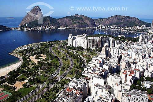Vista aérea do Aterro do Flamengo (1) com Morro da Viúva, Pão de Açúcar (2) ao fundo - Rio de Janeiro - 14/07/2005(1) Mais conhecido como Aterro do Flamengo, o Parque Brigadeiro Eduardo Gomes é a mais extensa área de lazer da cidade. Construído sobre aterramento de 1,2 milhão de metros quadrados tomados ao mar, abrange uma faixa de terra que se estende do Aeroporto Santos Dumont até o Morro da Viúva, em Botafogo. O projeto, inaugurado em 1964, foi coordenado por Maria Carlota (Lota) Macedo Soares e os projetos arquitetônico e paisagístico são respectivamente de Affonso Eduardo Reidy e Burle Marx.  É Patrimônio Histórico Nacional desde 28-07-1965.(2) É comum chamarmos de Pão de Açúcar, o conjunto da formação rochosa que inclui o Morro da Urca e o próprio Morro do Pão de Açúcar (o mais alto dos dois). Esse conjunto rochoso é Patrimônio Histórico Nacional desde 08-08-1973.  - Rio de Janeiro - Rio de Janeiro - Brasil