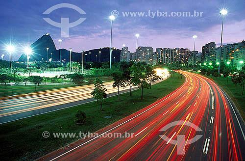 Vista noturna do Aterro do Flamengo ou Parque do Flamengo   com suas avenidas, prédios iluminados e ao fundo o Pão de Açúcar -  Rio de Janeiro - Brasil   Mais conhecido como Aterro do Flamengo, o Parque Brigadeiro Eduardo Gomes é a mais extensa área de lazer da cidade. Construído sobre aterramento de 1,2 milhão de metros quadrados tomados ao mar, abrange uma faixa de terra que se estende do Aeroporto Santos Dumont até o Morro da Viúva, em Botafogo. O projeto, inaugurado em 1964 e tombado em 1965, foi coordenado por Maria Carlota (Lota) Macedo Soares e os projetos arquitetônico e paisagístico são respectivamente de Affonso Eduardo Reidy e Burle Marx.  - Rio de Janeiro - Rio de Janeiro - Brasil