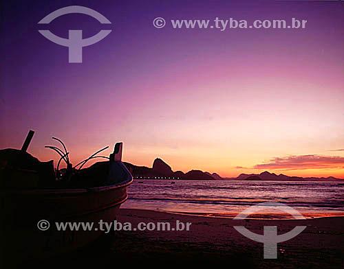 Praia de Copacabana ao nascer do sol com barco de pescador em primeiro plano e o Pão de Açúcar ao fundo - Rio de Janeiro - RJ - Brasil  - Rio de Janeiro - Rio de Janeiro - Brasil