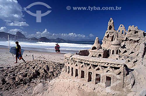 Castelo de areia na Praia de Copacabana, rapaz com prancha bodyboard e o Pão de Açúcar ao fundo - Rio de Janeiro - RJ - Brasil  - Rio de Janeiro - Rio de Janeiro - Brasil