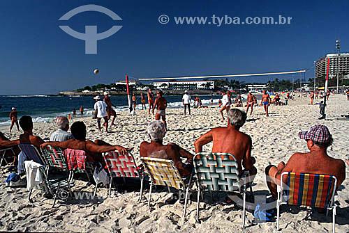 Homens sentados em cadeiras de praia assistindo jogo de voley na Praia de Copacabana com o Forte de Copacabana ao fundo - Rio de Janeiro - RJ - Brasil  - Rio de Janeiro - Rio de Janeiro - Brasil