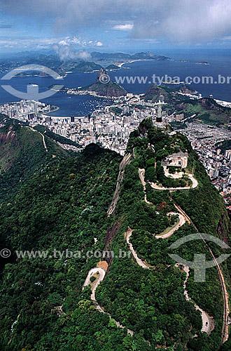 Vista aérea do Morro do Corcovado na floresta da Tijuca, com a estrada e o trilho do bonde que leva ao Cristo Redentor e ao fundo: os prédios da enseada de Botafogo, o Pão de Açúcar, a entrada da Baía de Guanabara e a cidade de Niterói - Rio de Janeiro - RJ - Brasil  é comum chamarmos de Pão de Açúcar, o conjunto da formação rochosa que inclui o Morro da Urca e o próprio Morro do Pão de Açúcar (o mais alto dos dois). Nesta foto, o pequeno Morro Cara de Cão, onde foi construído o Forte São João em 1578, é visto à esquerda como a parte mais baixa  e avançada sobre a Baía do mesmo complexo.  - Rio de Janeiro - Rio de Janeiro - Brasil