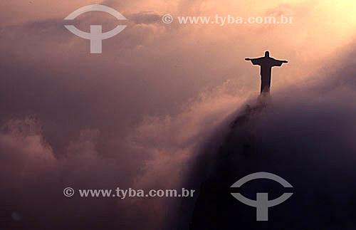 Silhueta do Cristo Redentor envolto em nuvens iluminadas pelo reflexo do pôr-do-sol - Rio de Janeiro - RJ - Brasil  - Rio de Janeiro - Rio de Janeiro - Brasil