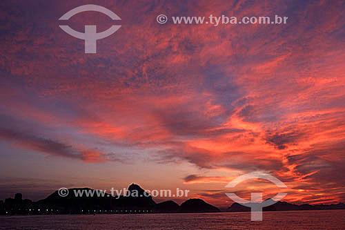 Silhueta do Pão de Açúcar na Baía de Guanabara com nuvens iluminadas e coloridas pelo reflexo do pôr-do-sol - Rio de Janeiro - RJ - Brasil  - Rio de Janeiro - Rio de Janeiro - Brasil