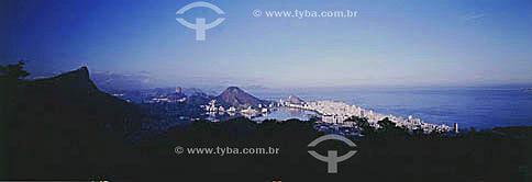 Vista aérea panorâmica do Cristo Redentor sobre o Morro do Corcovado na Floresta da Tijuca em primeiro plano na sombra e abaixo, no sol,  parte da Lagoa Rodrigo de Freitas   ; os prédios dos bairros de Ipanema e Leblon à direita e o Pão de Açúcar à esquerda ao fundo - Rio de Janeiro - RJ - Brasil  Patrimônio Histórico Nacional desde 19-06-2000.  - Rio de Janeiro - Rio de Janeiro - Brasil
