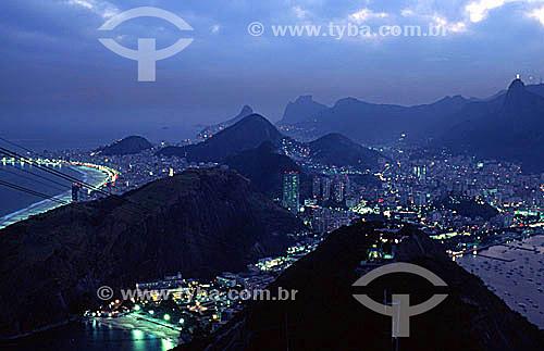 Vista de parte da zona sul da cidade, iluminada ao cair da noite, a partir do Pão de Açúcar. A Praia Vermelha em primeiro plano abaixo, ladeada pelo Morro da Babilônia; seguida da Praia de Copacabana à esquerda; e do Morro dos Dois Irmãos e da Pedra da Gávea mais ao fundo. À direita, os prédios do bairro de Botafogo e o Cristo Redentor sobre o Morro do Corcovado ao fundo - Rio de Janeiro - RJ - Brasil  - Rio de Janeiro - Rio de Janeiro - Brasil