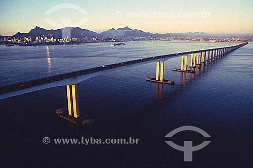 Vista aérea da Ponte Rio-Niterói  na Baía de Guanabara com os prédios do centro da cidade do Rio de Janeiro e o relevo montanhoso da cidade ao fundo - RJ - Brasil / Data: 2007  A Ponte Rio-Niterói, cujo verdadeiro nome é Ponte Presidente Costa e Silva, tem 13.290m de extensão, liga a cidade do Rio de Janeiro à cidade de Niterói e foi inaugurada em 1974. A viga reta metálica do vão central sobre o canal de navegação, é uma das maiores no mundo, com mais de 970 mil toneladas, o que corresponderia a 800 edifícios de 10 andares, com quatro quartos.