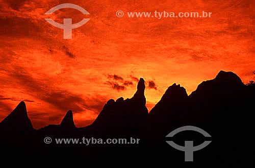 Pôr-dol-sol desenhando a silhueta do conjunto de montanhas mais representativo do Parque Nacional da Serra dos Órgãos, entre os quais se destaca o Dedo de Deus, pico assim denominado por sugerir a forma de um dedo indicador apontado para o céu - Teresópolis - Região serrana do estado do Rio de Janeiro - Brasil  - Teresópolis - Rio de Janeiro - Brasil