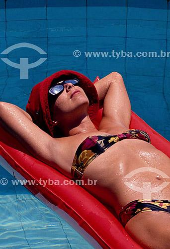 Mulher boiando na piscina de biquini e óculos escuros