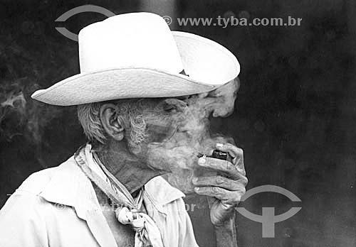 Terceira idade, senhor velho  fumando cachimbo e usando chapéu