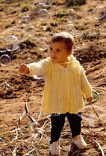 Menina brincando com bolhas de sabão