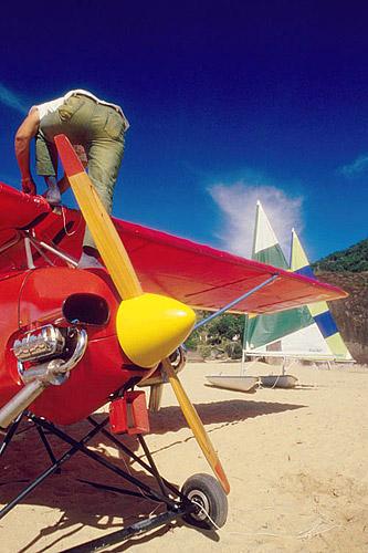 Homem em avião à hélice e barco à vela - Manguaratiba - RJ - Brasil  - Rio de Janeiro - Brasil