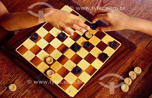 Mãos movimentando peças de jogo de damas