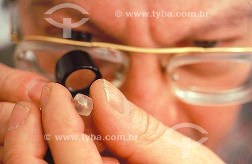 Joalheiro verificando qualidade de um diamante com uma lupa - Pedra preciosa