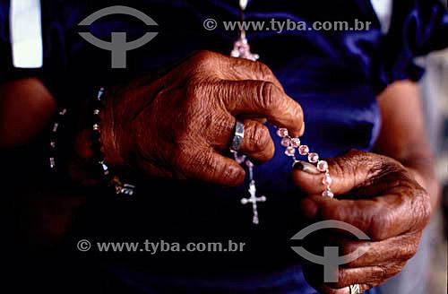 Detalhe das mãos de uma idosa rezando com um rosário com uma cruz