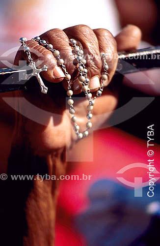 Detalhe de mão com terço e crucifixo, em missa noturna na cidade de Bom Jesus da Lapa, uma manifestação importante da fé católica no Brasil - Bahia  - Bom Jesus da Lapa - Bahia - Brasil