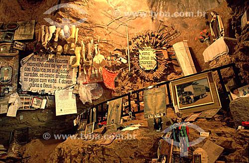 Fotografias, imagens de santos e esculturas em cera de partes do corpo humano, em sala dedicada aos ex-votos no interior da gruta do Santuário de Bom Jesus da Lapa, uma manifestação importante da fé católica - Bom Jesus da Lapa - Bahia - Brasil  - Bom Jesus da Lapa - Bahia - Brasil