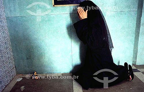 Mulher vestida de preto ajoelhada rezando