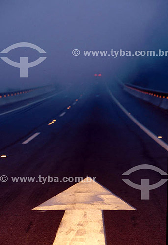 Seta de sinalização de trânsito em estrada com neblina - Brasil