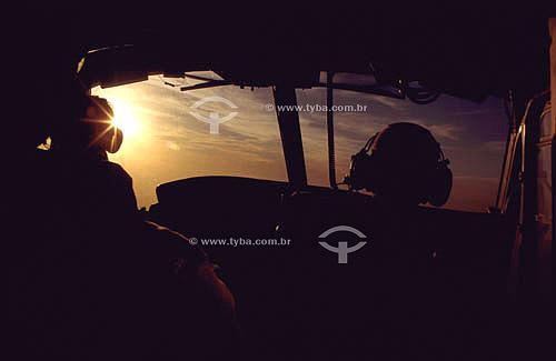 Interior de cabine de comando do avião com piloto e co-piloto em silhueta