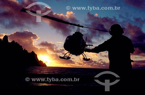 Transporte de carga - silhueta de homem orientando pouso de helicóptero ao pôr-do-sol  no convôo  do Barão de Teffé - Ilha da Trindade - Es - Brasil   heliponto em navios  - Espírito Santo
