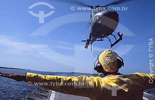 Helicóptero pousando no Navio Hospitalar Oswaldo Cruz e controlador de vôo com protetor para o ouvido em primeiro plano - Amazônia - Brasil