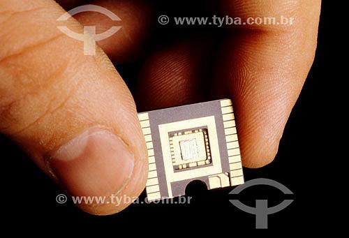 Detalhe de mão segurando um chip de computador