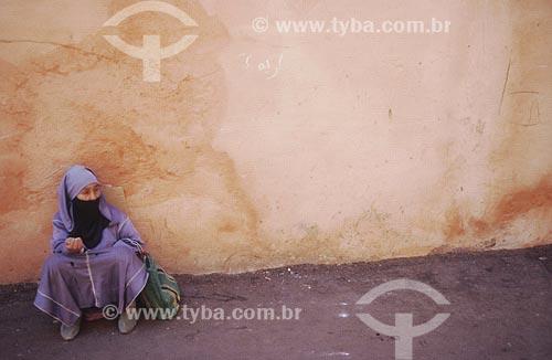 Assunto: Mulher com vestimenta típica, sentada no chãoLocal: Marrocos, ÁfricaData: