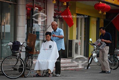 Assunto: No distrito de Guomao um cabeleireiro que utiliza sua bicileta como salão corta os cabelos de seu cliente  / Local:  Pequim - China  / Data: Agosto de 2008