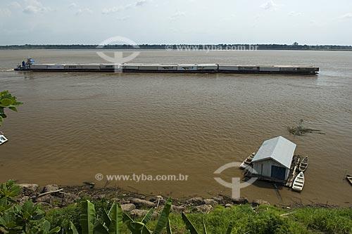 Assunto: Casa flutuante na margem do rio Amazonas com uma balsa carregada de contêineres no fundo  / Local:  Itacoatiara - Amazonas (AM) - Brasil  / Data: 11/2007