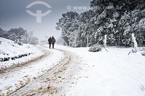Assunto: Casal caminhando em estrada de terra coberta de neve / Local: Urubici - Santa Catarina (SC) - Brasil / Data: 04/08/2010