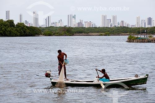 Assunto: Pescador praticando pesca de rede  na Ilha de Deus com prédios da Praia de Boa Viagem ao fundo   / Local:  Recife - Pernambuco  / Data: 14/10/2010