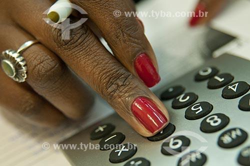 Assunto: Detalhe de mão feminina e calculadora  / Local:  / Data: 10/2010